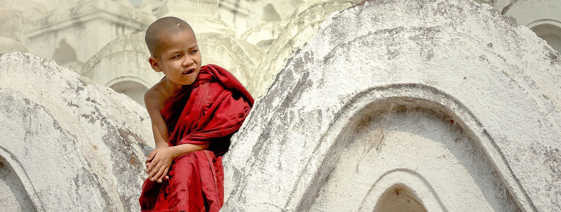 A novice sitting at a pagoda in Mandalay