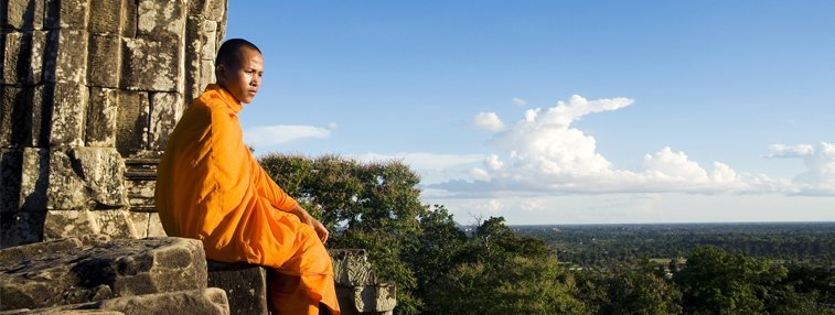 A monk siting at the top of the mountain