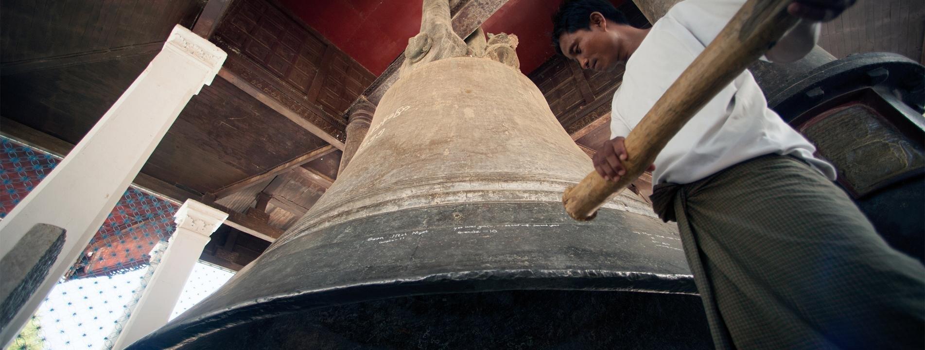 Man hitting the world's largest bronze bell in Mingun