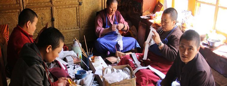 Nuns are making amulets with pieces of Buddhism scripts