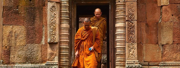 two monks walking out of a temple of angkor wat